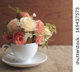 vintage roses in a cup on brown ... | Shutterstock . vector #165437573