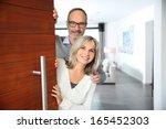 senior couple welcoming people... | Shutterstock . vector #165452303