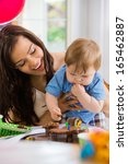 happy mother looking at baby... | Shutterstock . vector #165462887