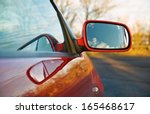 The Wing Mirror Of A Red Car A...
