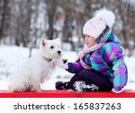 Stock photo girl playing with a white dog winter snow happiness 165837263