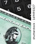 Small photo of Ratingen, Germany - June 21, 2011: Closeup of green American Express credit card on a number pad. AMEX is one of the biggest credit card companies worldwide. Studio shot.
