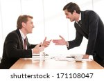 Small photo of Business conflict. Two young men in formalwear arguing and gesturing while sitting at the table