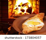 Small photo of adzharia hachapuri with egg on plate and open fire in wood burning stove