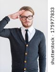 Small photo of Yes sir! Handsome young man in glasses holding hand near head and looking at camera while standing against grey background