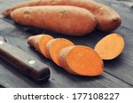 Raw Sweet Potatoes On Wooden...