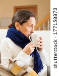 Small photo of Ailing middle-aged woman sitting on couch with cup of tea