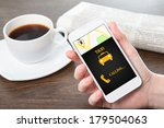 Small photo of businesswoman hand holding a phone with interface taxi against the background of the table in the office