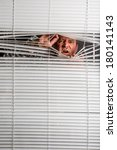 Small photo of Agoraphobia. A man looking through window blind with facial expressions.