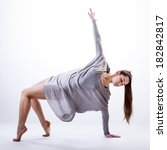 Small photo of A female contemporary dancer in a flowy grey dress practising and stretching