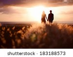 Small photo of Young couple enjoying the sunset in the meadow