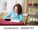 Small photo of Finances: Pretty Woman Writing Checks and Paying Bills