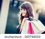 happy woman holding shopping... | Shutterstock . vector #183746033