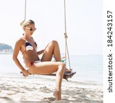 blonde woman on swing on beach...   Shutterstock . vector #184243157