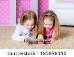 sisters using a tablet computer  | Shutterstock . vector #185898113