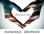 Stock photo memorial day written in the blank space of a heart sign made with the hands patterned with the 186196103
