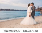 groom kissing bride on beach | Shutterstock . vector #186287843