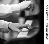 Small photo of Hands pianist playing on a grand piano in black and white