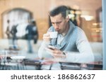 young man drinking coffee in... | Shutterstock . vector #186862637