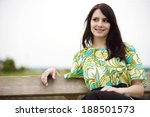 Small photo of Observant thoughtful young woman sitting relaxing on an old rustic wooden bench outdoors looking to the side with a pensive expression, with copy space
