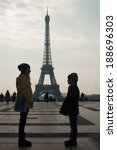 Small photo of Boy and girl standing beforehand Eiffel tower