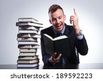 Small photo of young business man reading at an office with a stack of books and pointing up with a smile on his face, as he understands the idea. on a light studio background