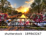 Stock photo beautiful sunrise over amsterdam the netherlands with flowers and bicycles on the bridge in spring 189863267
