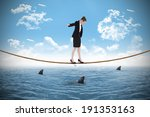 Small photo of Businesswoman performing a balancing act over shark infested sea under blue sky