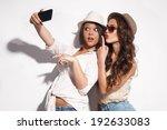 two young women taking selfie...