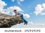 Small photo of acrophobia teenager boy man stands on the precipice of a cliff height and fear of heights on a background of blue sky