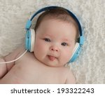 Stock photo cute baby boy wearing blue headphones and sticking tongue out 193322243