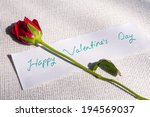 """Small photo of Red Rose lying on white cloth with a note """"Happy Valentines Day"""" written on it"""