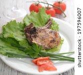 pork steak on lettuce with...