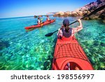Two Men Paddle A Kayak On The...