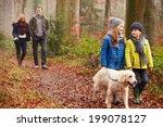 Stock photo family walking dog through winter woodland 199078127