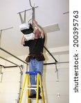 man standing on a ladder fixing ... | Shutterstock . vector #200395763
