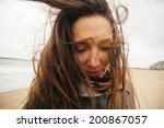 young woman on windy beach ... | Shutterstock . vector #200867057