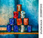 Small photo of Pyramid of ten empty soup cans of white, blue and red colors against grunge metal wall. Some cans are shot through. Soup Cans - Square Meal. Andy Warhol inspired.