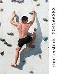 Young Man Climbs Up An Outdoor...