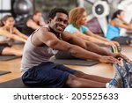 Small photo of Young African-American man stretching in a gym and looking to camera
