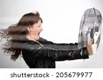 Small photo of Beautiful woman is screaming with a ventilator in your hands