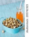Small photo of Snack of caramel popcorn with orange soda pop with straw