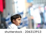 Small photo of NEW YORK CITY - JULY 20 2014: several thousand supporters of Israeli actions in Gaza staged a rally in Times Square. Yarmulka wearing boy with Israeli flags background