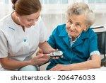 female nurse measuring blood... | Shutterstock . vector #206476033