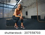 young woman sitting on a box at ... | Shutterstock . vector #207558703