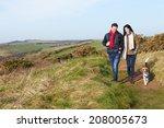 Stock photo couple with dog walking along coastal path 208005673