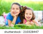 two little girls are reading... | Shutterstock . vector #210328447