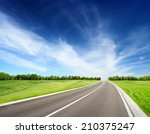 asphalt road between grassy... | Shutterstock . vector #210375247