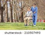 Male Nurse Pushing A Senior In...