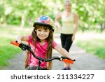 mom and daughter ride bikes in... | Shutterstock . vector #211334227